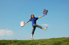 Girl jumping. With the shopping bags royalty free stock photo