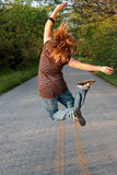 Girl Jumping. Teenage girl jumping in the air opposite direction with hands and feet up while in the middle of a road royalty free stock photos