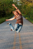 Girl Jumping. Teenage girl jumping in the air opposite direction with hands and feet up while in the middle of a road stock photos