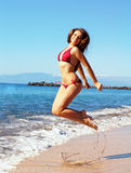 Girl jumping. Yong beautiful girl jumping at the beach on a sunny day Royalty Free Stock Photography