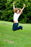 Girl Jumping. A teenage girl jumping in the park Stock Photo