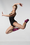 Girl jumping. Sport style girl in black swimsuit jumping Stock Image