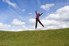 Girl jumping. On grass and blue background Royalty Free Stock Photos