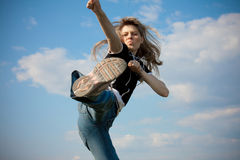 Girl jumping. Outside with blue sky in background Royalty Free Stock Photography