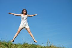 Girl jumping against the beautiful sky Royalty Free Stock Image