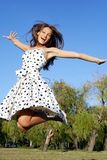 Girl jumping against blue sky Stock Images