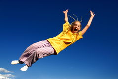 Girl jumping in air. Blue sky in background Stock Photos