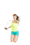 Girl jumping in the air with headphones showing thumbs up Stock Image