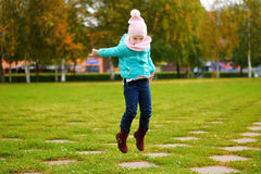 Girl jumping in autumn park Stock Photos