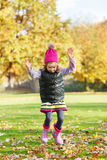 Girl jumping in autumnal park. Cute preschool girl jumping in autumnal park royalty free stock image