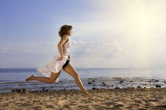 Girl jumping on the beach Stock Photos