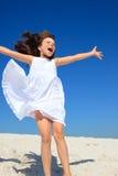 Girl jumping on beach Stock Photos