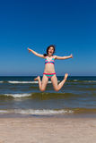 Girl jumping on beach royalty free stock photos