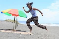 Girl jumping on beach by parasol. Young Papuan woman - smiling pretty girl jumping in running pose on sandy beach with dark sand by red, green and yellow parasol royalty free stock photo