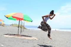 Girl jumping on beach by parasol. Young Papuan woman - smiling pretty girl jumping in running pose on sandy beach with dark sand by red, green and yellow parasol royalty free stock images