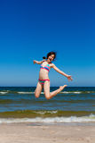 Girl jumping on beach Royalty Free Stock Image