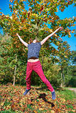 Girl jumping in beautiful autumn park Royalty Free Stock Image