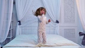 Girl is jumping on the bed stock footage