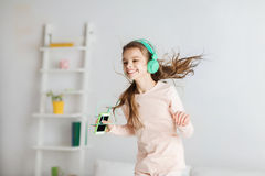 Girl jumping on bed with smartphone and headphones Stock Images