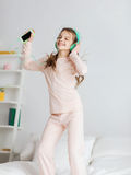 Girl jumping on bed with smartphone and headphones Stock Image