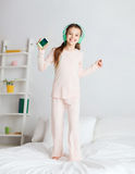 Girl jumping on bed with smartphone and headphones Royalty Free Stock Images