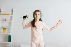 Girl jumping on bed with smartphone and headphones Stock Photos