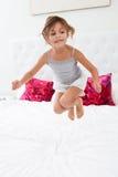 Girl Jumping On Bed Wearing Pajamas Stock Photos