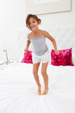Girl Jumping On Bed Wearing Pajamas Stock Photos