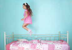 Girl jumping on bed. 8 years old girl jumping on the bed at home Royalty Free Stock Image