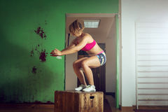 Girl jumping on box in gym Stock Photos