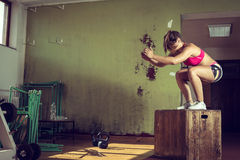 Girl jumping on box in gym Royalty Free Stock Images