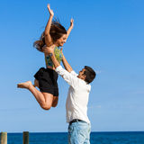 Girl jumping into boys arms Stock Images