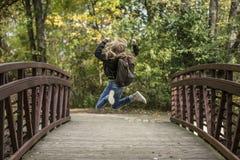 Girl Jumping on the Bridge Wearing Black Jacket stock image