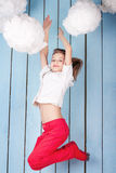 Girl jumping in the clouds Stock Images