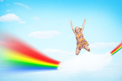 Girl jumping on clouds and a rainbow Stock Photos