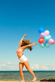 Girl jumping with colorful balloons on beach Royalty Free Stock Photos