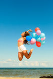 Girl jumping with colorful balloons on beach Stock Images