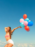 Girl jumping with colorful balloons on beach Stock Photos