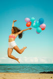 Girl jumping with colorful balloons on beach Royalty Free Stock Images