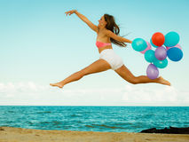 Girl jumping with colorful balloons on beach Royalty Free Stock Image