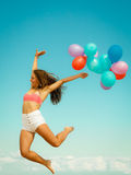 Girl jumping with colorful balloons on beach Stock Photography