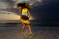 Girl jumping and dancing on beautiful beach. Stock Photography