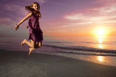 Girl jumping and dancing on beautiful beach. Stock Image