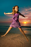 Girl jumping and dancing on beautiful beach. Stock Photo