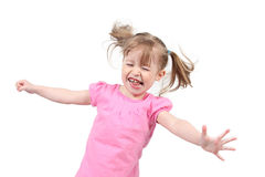 Girl jumping with eyes closed. Female toddler jumping with outstretch arms and eyes closed, isolated on white background royalty free stock photo