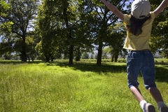 Girl jumping in field Stock Photography