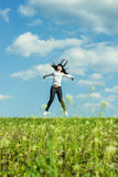 Girl jumping in the field summer time Royalty Free Stock Images