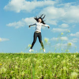 Girl jumping in the field summer time Royalty Free Stock Image