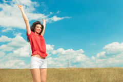 Girl jumping in the fields with her hands raised in the air Royalty Free Stock Images