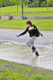 Girl jumping through flood on road Stock Image